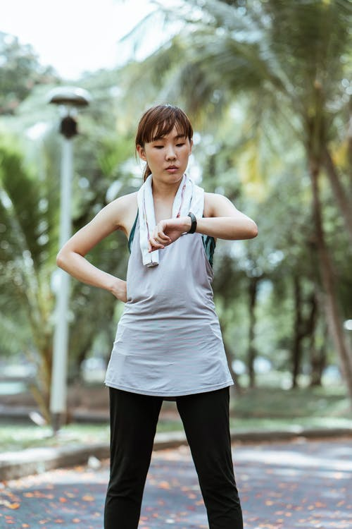 Slim Asian sportswoman in activewear and towel using wearable bracelet while standing with hand on waist on asphalt pavement in park in daylight