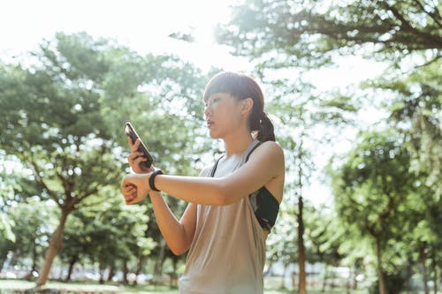 Asian sportswoman using smart watch and smartphone during training