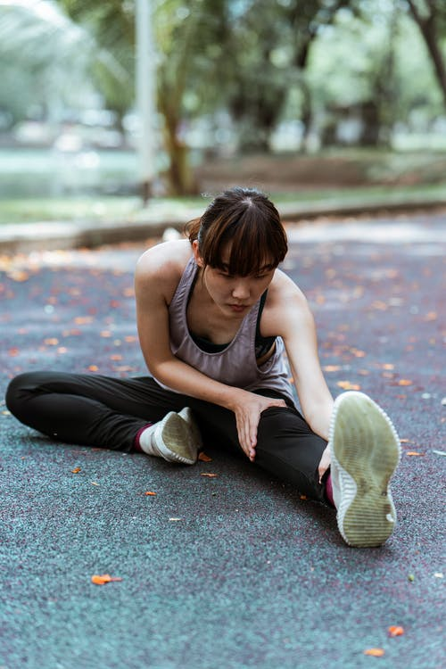 Slender flexible young Asian woman in activewear sitting on asphalt embankment doing bend forward while practicing yoga in park in fall