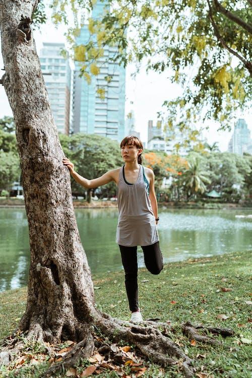 Asian sportswoman exercising in city park near pond in daylight