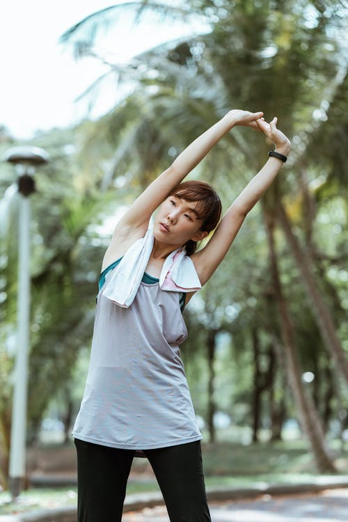 Asian sportswoman doing side bend in park in daylight