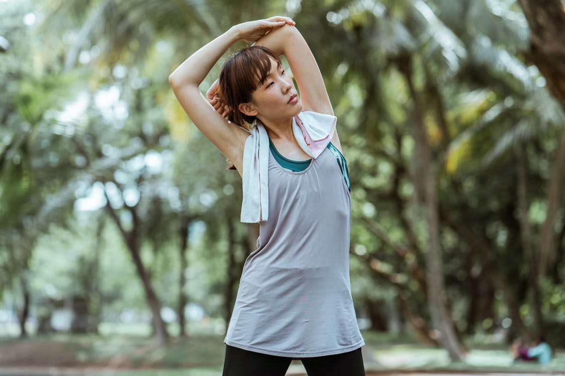 Fit young Asian female athlete with cotton towel in sportswear doing side bend while looking away in park with green trees in daylight
