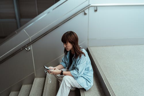 From above side view of pensive Asian female in casual clothes browsing internet on cellphone while sitting on stairs with earphones in building