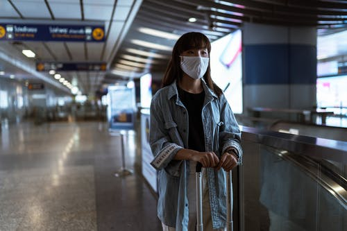 Woman Wearing a Face Mask and Waiting at a Station