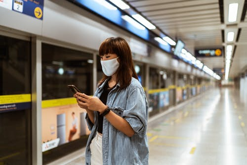 Woman Wearing a Face Mask and Using her Smartphone