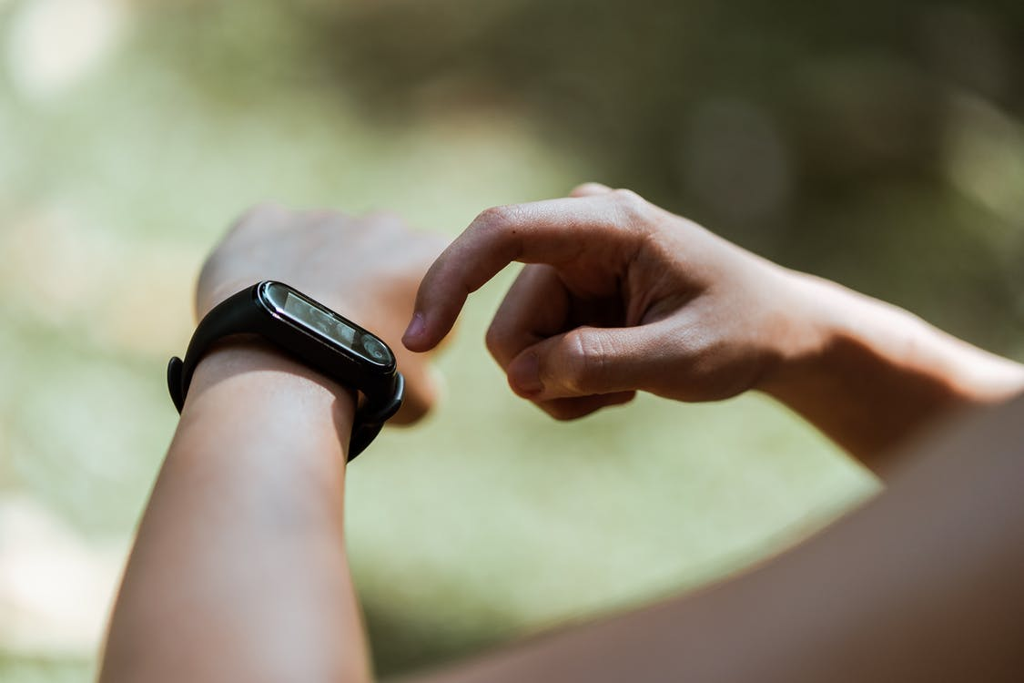 Crop unrecognizable person using smart watch outdoors