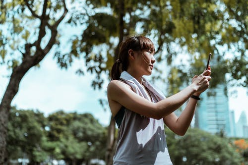 From below side view of slender Asian female athlete in sports clothes with towel taking selfie on mobile phone while standing near trees under sky and looking away