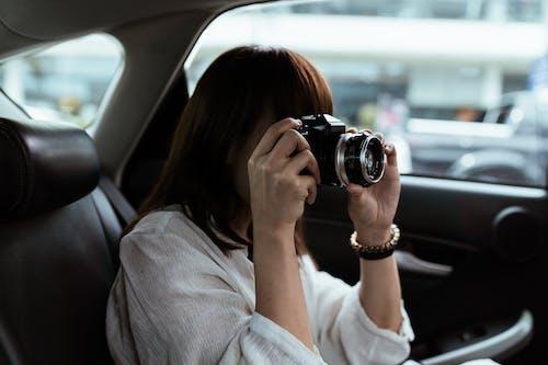 Unrecognizable female traveler taking photo on photo camera in automobile