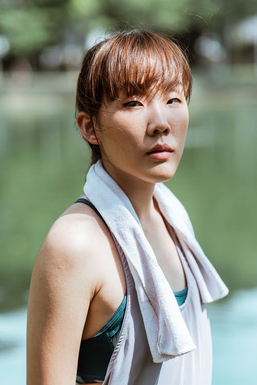 Side view of fit dreamy Asian female athlete in sports clothes with cotton towel on shoulders having break in park near pond and looking at camera