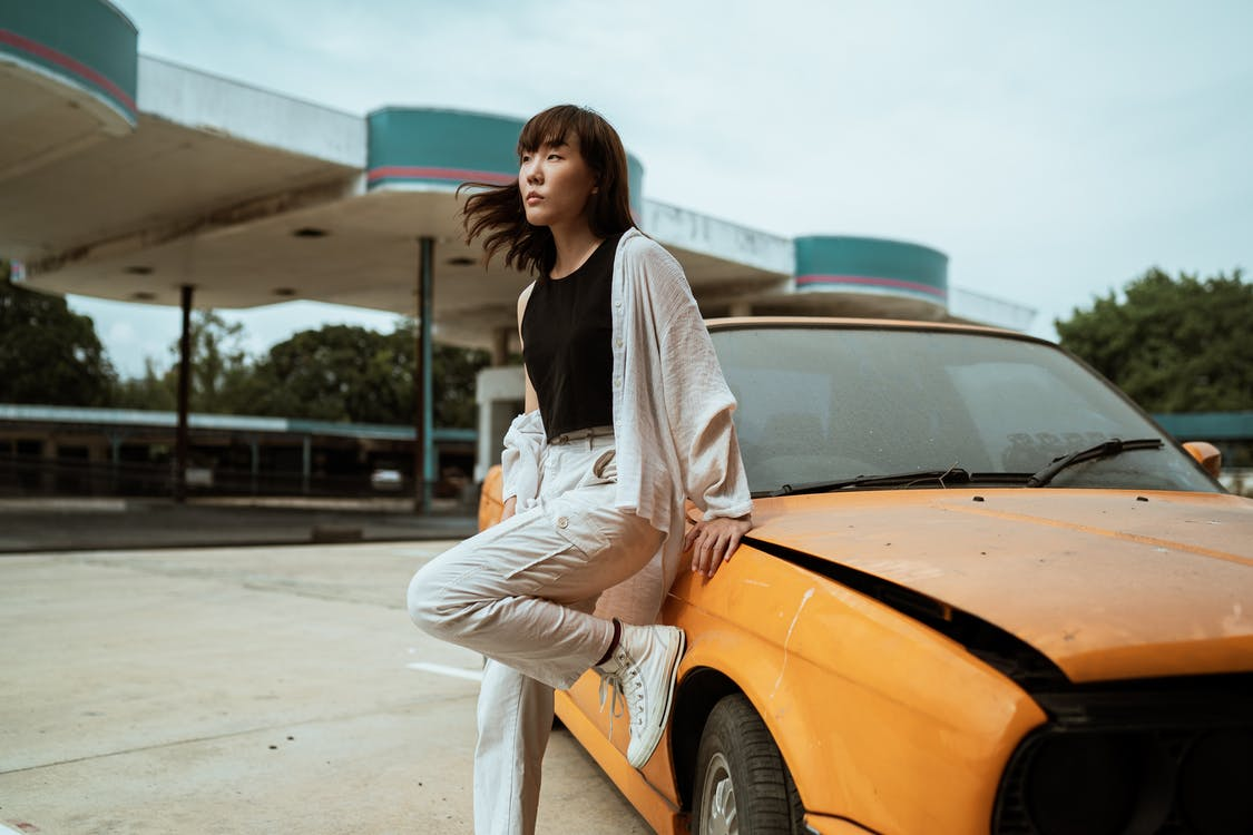 Slender young Asian female in casual wear looking away while standing leaned on one leg near old fashioned car parked on asphalt road on windy weather under cloudy sky