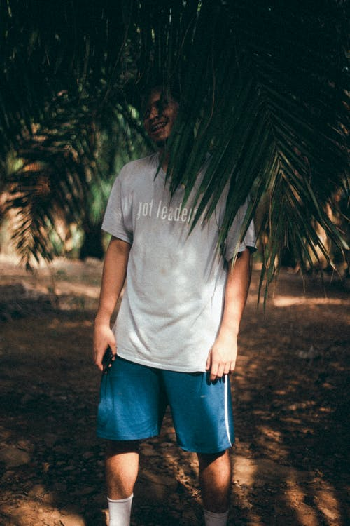 Man in Gray Crew Neck T-shirt and Blue Denim Jeans Standing Near Green Palm Tree