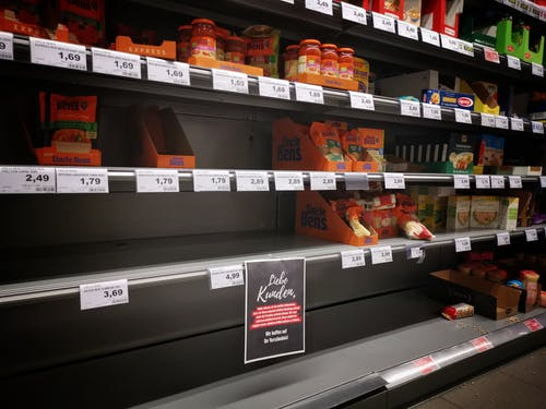 Half empty shelves with assorted products in jars and containers in supermarket during quarantine