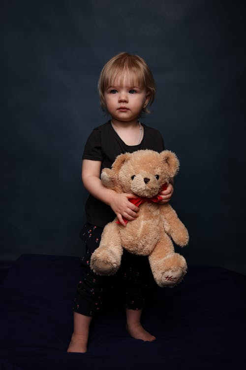 Adorable little girl in sleepwear standing on comfortable soft bed with teddy bear in hands
