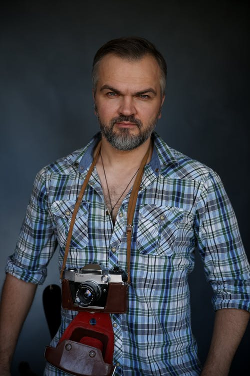 Serious adult bearded male photographer with old fashioned camera around neck in checkered shirt standing against gray background and looking at camera