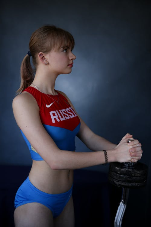 Strong slim sportswoman with dumbbell during training