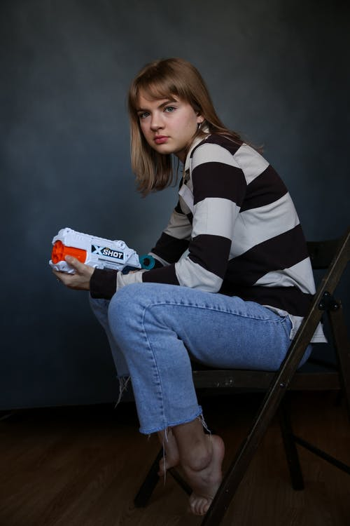 Relaxed young lady sitting on chair and looking at camera