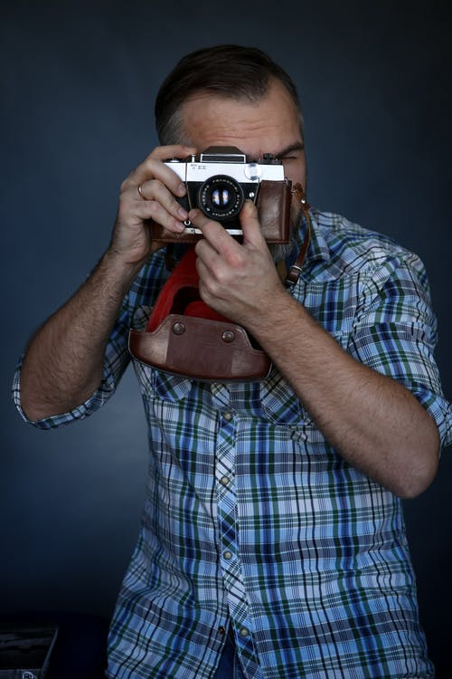 Unrecognizable male photographer in checkered shirt taking pictures on old fashioned film camera while working in studio