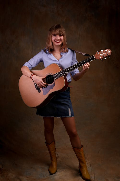 Full body of young happy female musician in casual outfit smiling while playing acoustic guitar in brown studio