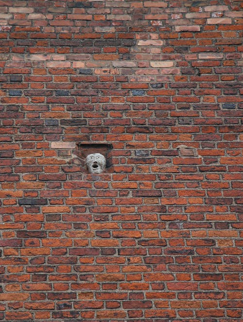 Old brick building with spooky mask