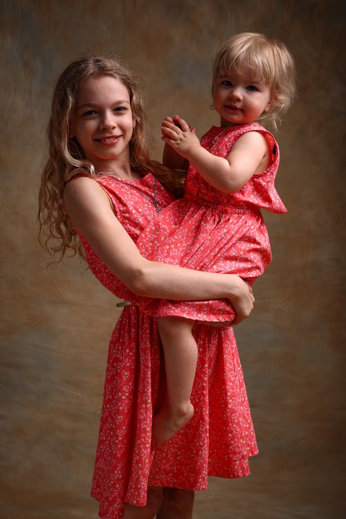 Side view of happy female teenager in romantic dress hugging adorable little sister and looking at camera