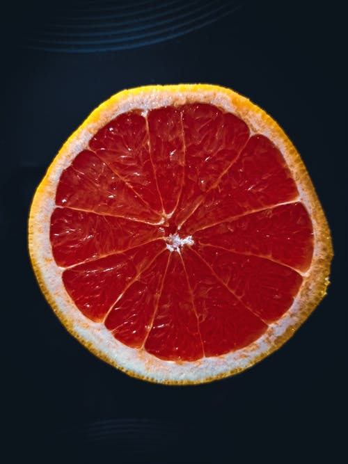 Top view of slice of fresh ripe juicy grapefruit placed on black surface