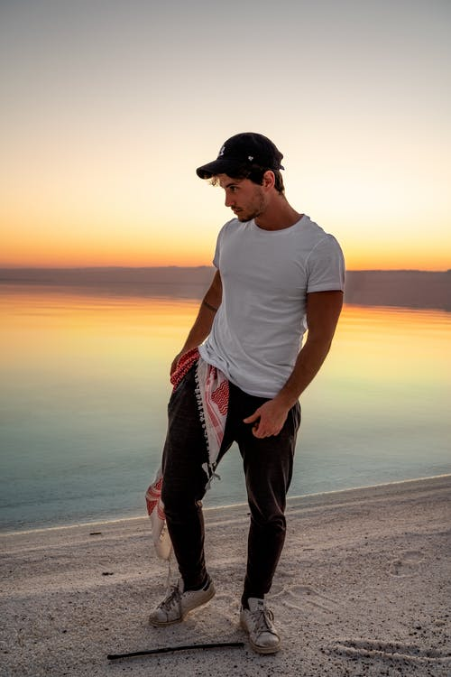 Young man standing on sandy lake shore at sunset