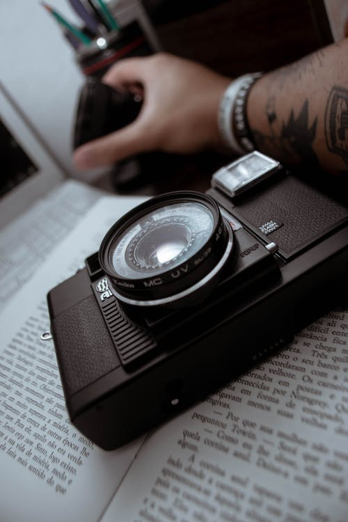 Black and Silver Camera on White Paper
