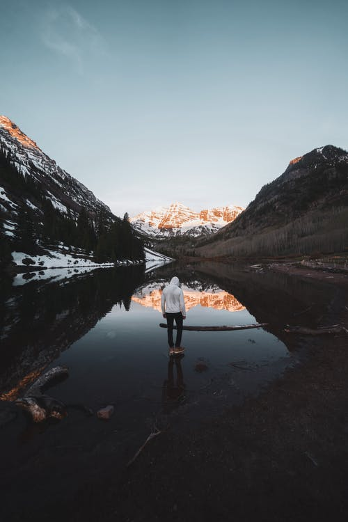 Faceless tourist standing near pond in mountainous valley in winter