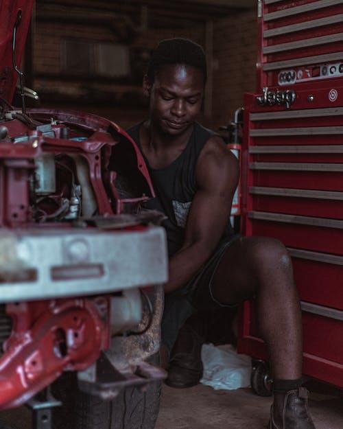 Young black man repairing vehicle in workshop