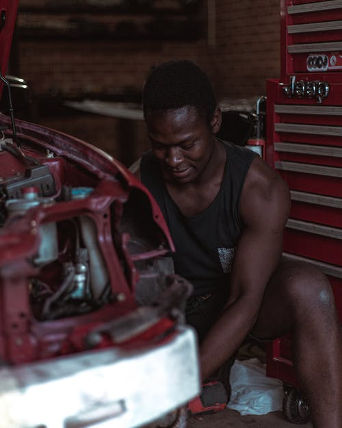Concentrated ethnic repairman fixing car in workshop