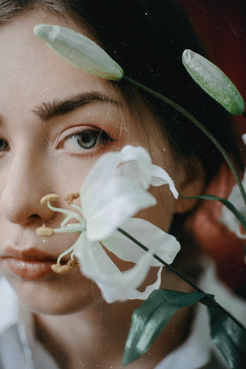 Dreamy young woman with gentle lily flowers