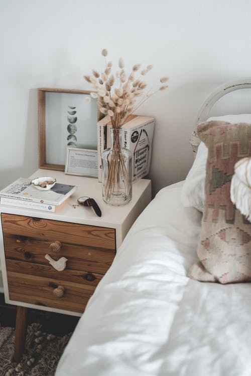 Cozy light interior of comfy bed and bedside table