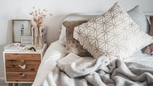 White and Brown Throw Pillow on White Bed