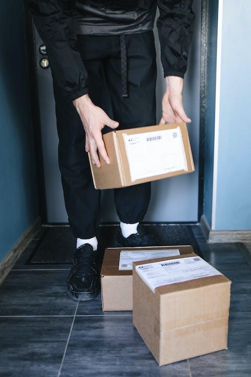 Man in Black Suit Holding Brown Cardboard Box