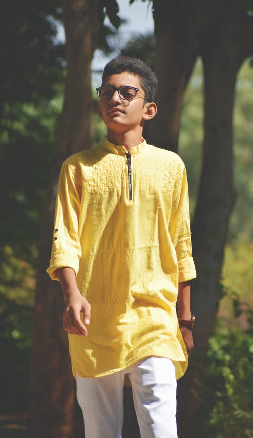 Serious ethnic teen boy wearing traditional clothes strolling in green park in sunny day