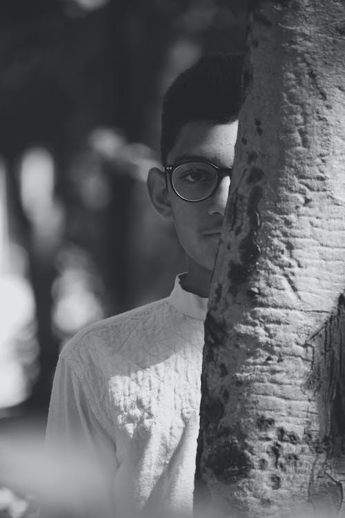 Ethnic man in eyeglasses behind tree trunk