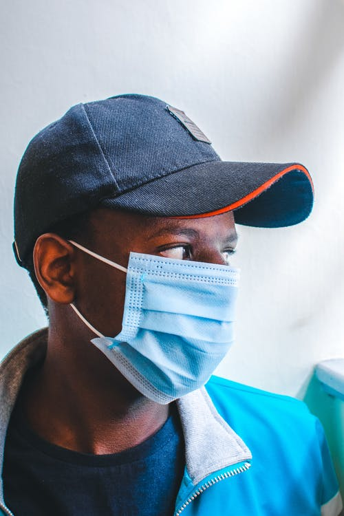 Black male in medical mask looking away