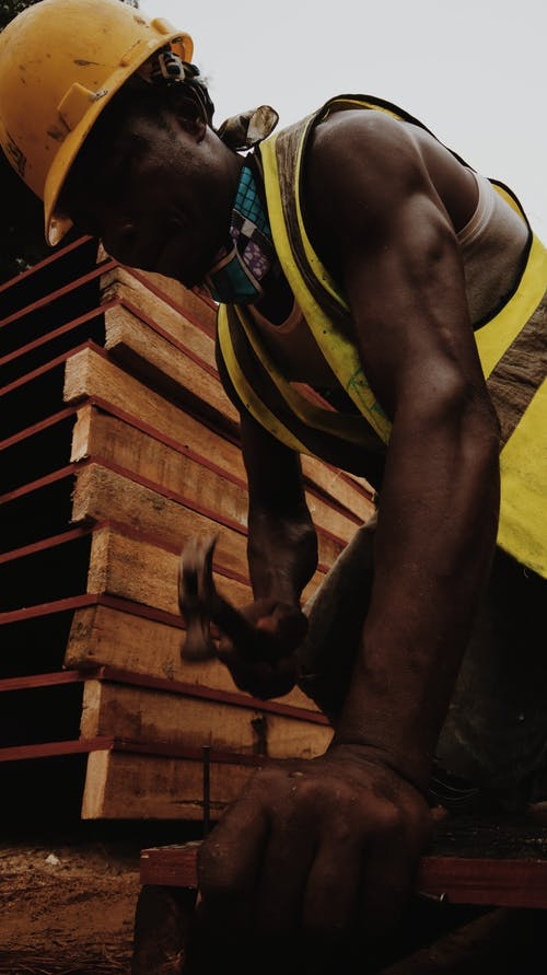 Focused black man hammering nail working in construction site