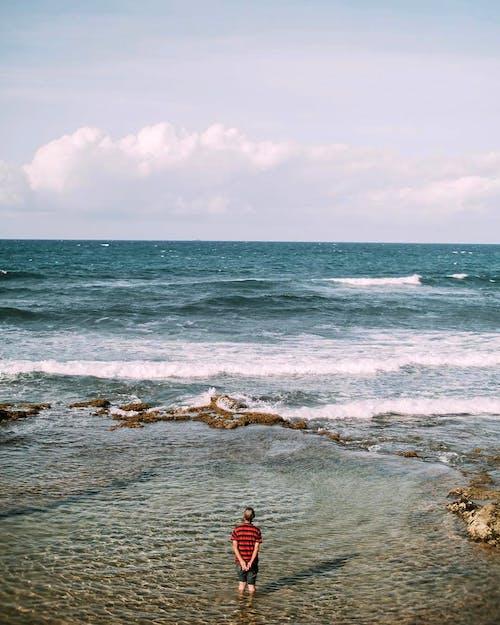 Man standing in water of foaming sea