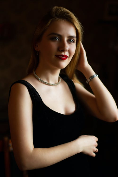 Positive young female wearing black dress and elegant jewelry on ears and neck