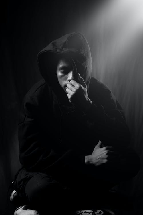 Black and white sad man wearing black hoodie sitting with eyes closed and covering face with hood