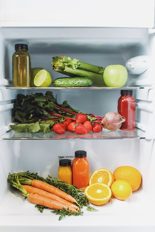 Green and Orange Fruits in Refrigerator