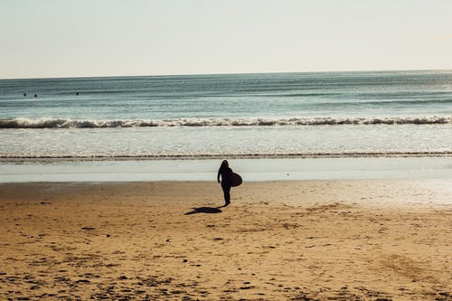 Full body silhouette of person holding surfboard and walking on sandy beach to vibrant ocean under light blue cloudless sky