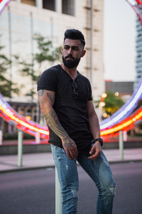 Confident bearded ethnic male with tattoos in casual clothes leaning on metal pole in urban area while looking away and contemplating