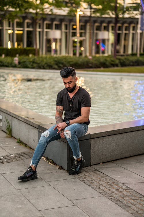 Full length of bearded ethnic man in casual outfit sitting on stone border and thinking while looking down in urban area