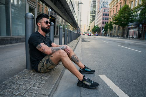 Side view of full body of bearded ethnic man in casual wear and sunglasses resting on sidewalk while sitting at pavement near road in city street