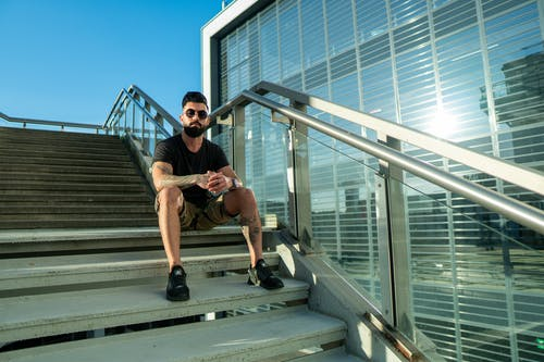From below of full body of bearded brutal ethnic man in casual clothes resting on stairs near modern glass building in urban area