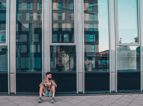 Ethnic man in trendy clothes sitting at modern glass city building on pavement