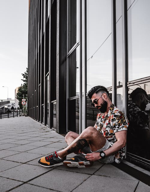 Side view of full body of bearded ethnic man in stylish clothes relaxing with crossed legs on pavement in urban area near contemporary glass building