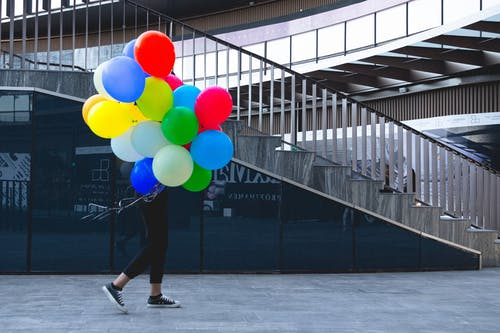 Person in Black Pants and Black Shoes Holding Multi Colored Balloons